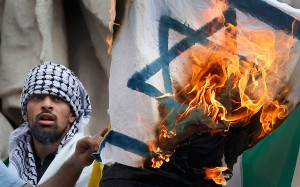 Pro Palestinian protester burns an Israeli flag during banned demonstration in support of Gaza in central Paris